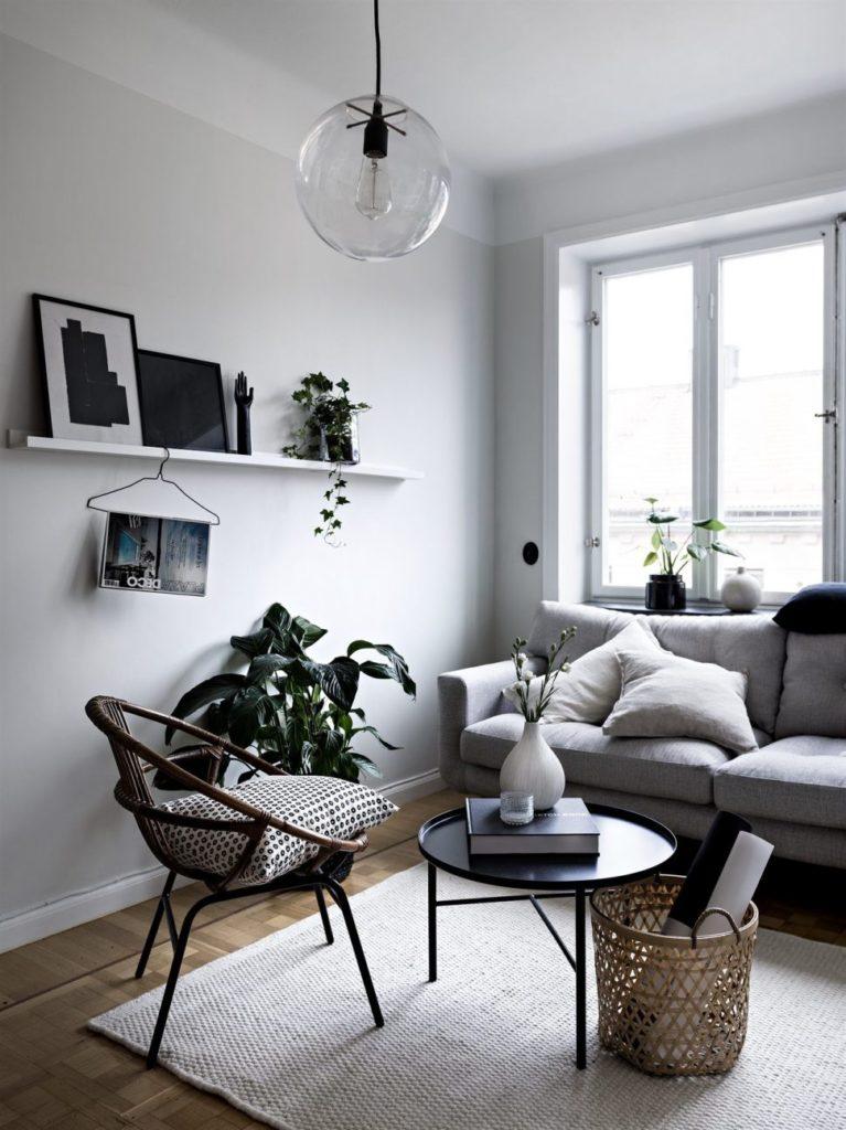 Sala minimalista, com móveis brancos e pretos, com linhas retas.