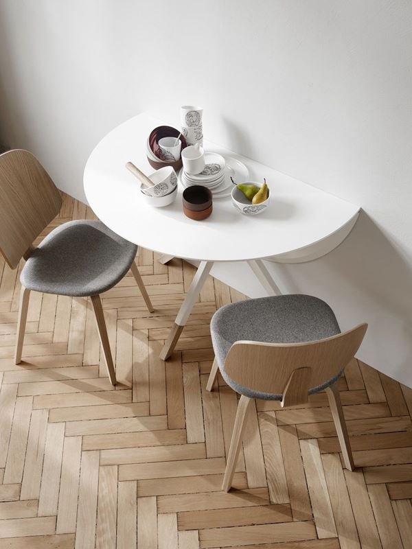 Mesa branca dobrável, com cadeira cinza com encosto de madeira.