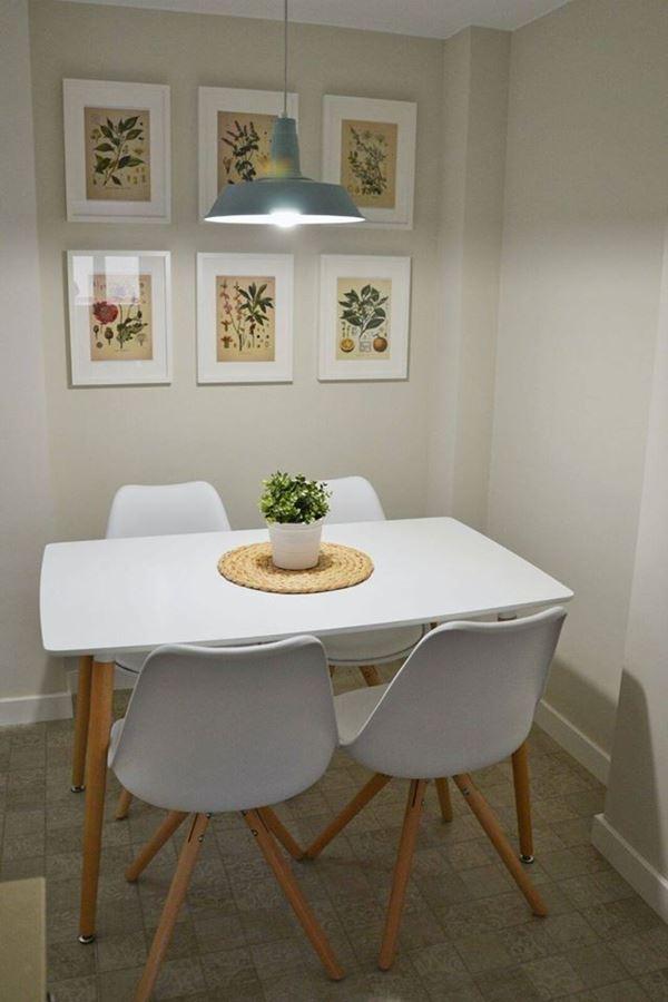 Mesa de jantar branca, com cadeiras da mesma cor e seis quadros na parede. Em cima, uma luminária cinza.