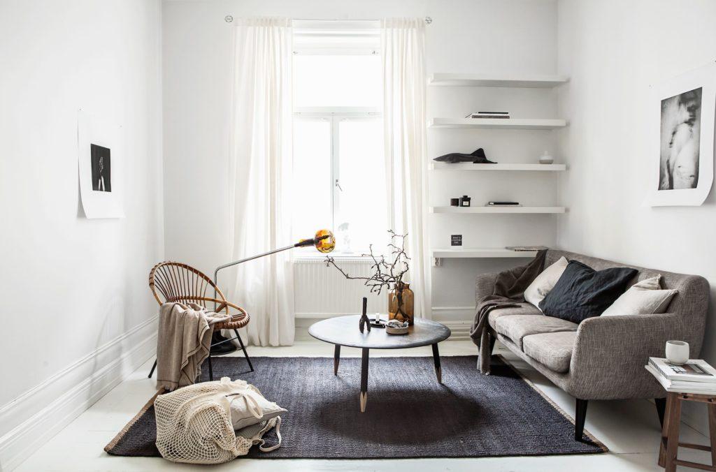 Sala minimalista, decorada com um sofá cinza, uma mesa de centro, uma poltrona de palha e uma estante branca.
