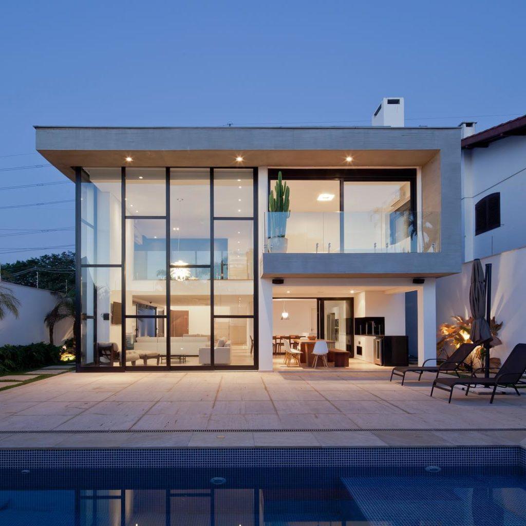 Casa de dois andares com parede toda de vidro e estrutura de metal.