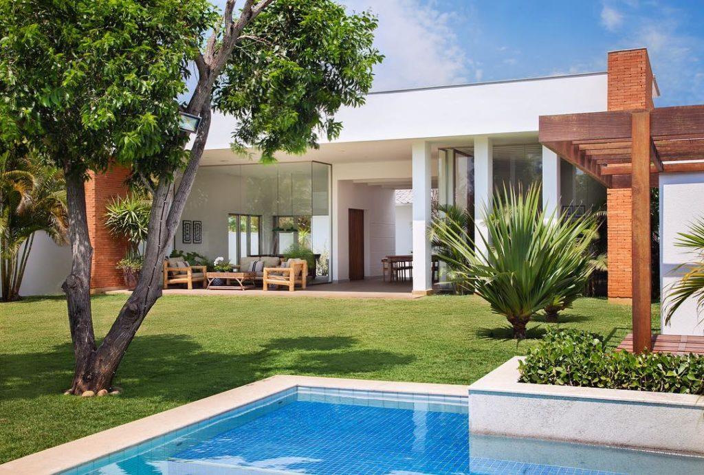 Área externa de casa com piscina e jardim.