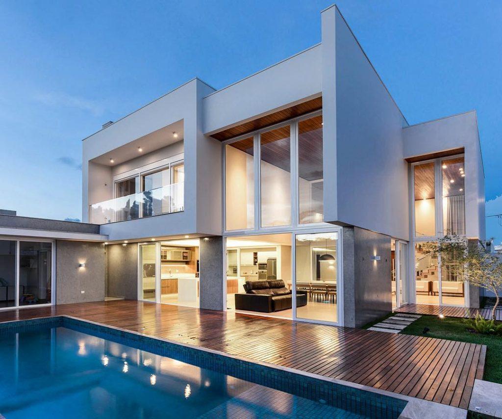 Casa de dois andares, com bastante vidro na fachada e pé direito alto.