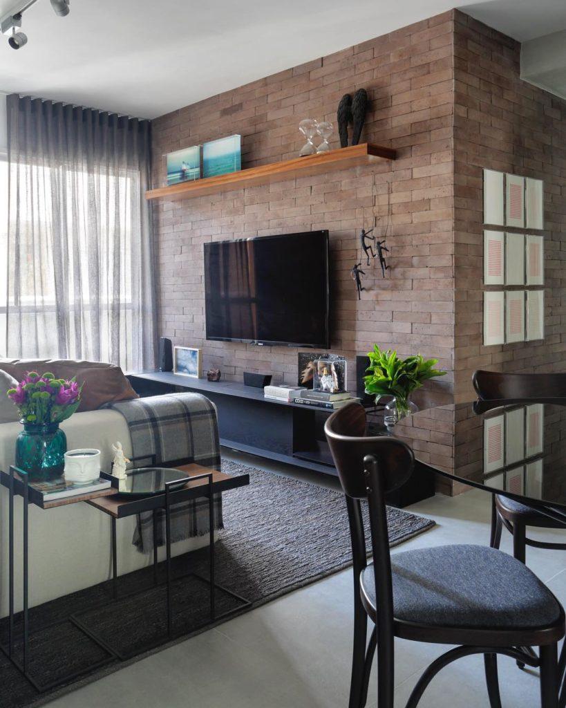 Sala com parede de tijolo, cortina cinza fluida, sofá branco, rack preto e tapete cinza.