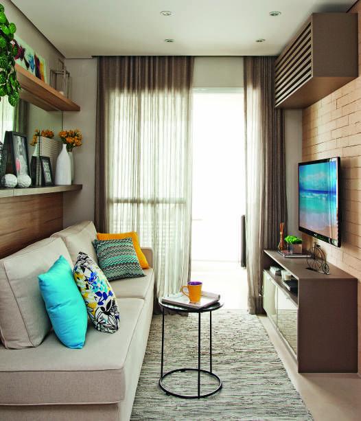 Sala com paredes de tijolo, rack cinza e sofá bege. Atrás do sofá, está um espelho com uma estante.