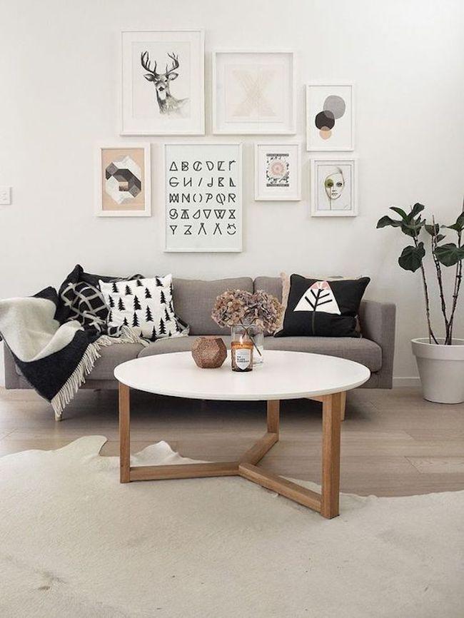 Ambiente com parede brancas, jogo de quadros, sofá cinza e mesa de centro também branca