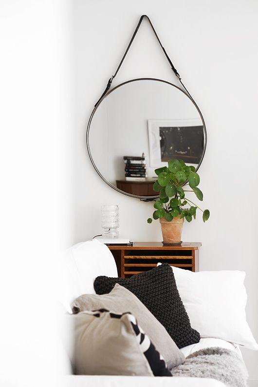 Espelho redondo moderno em canto, em cima de estante.