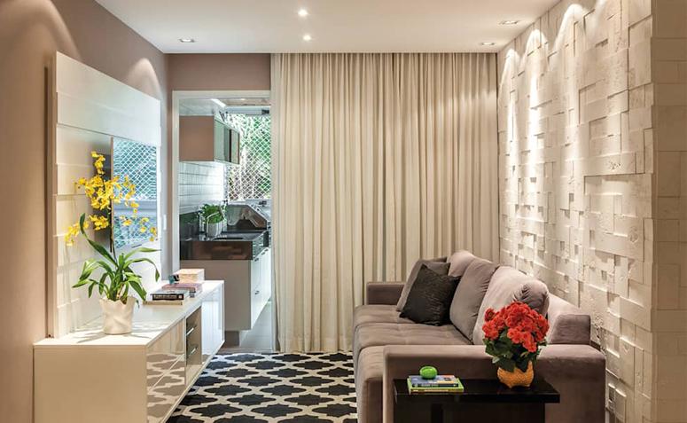 Sala com parede e cortinas bege, sofá cinza, rack branco e tapete preto.