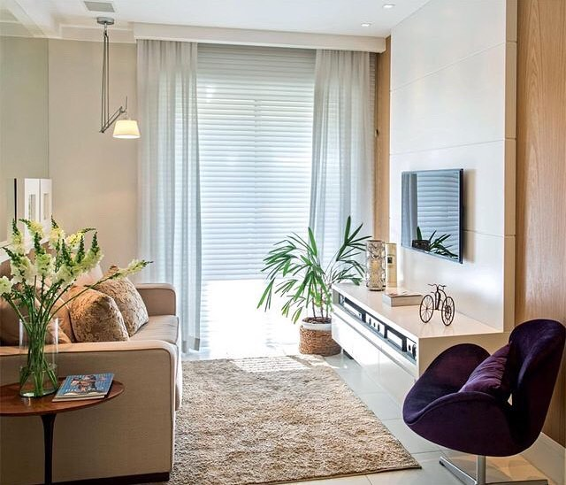 Sala de estar com sofá e tapetes nude, hack branco com madeira, duas plantas e objetos de decoração, além de uma poltrona roxa.