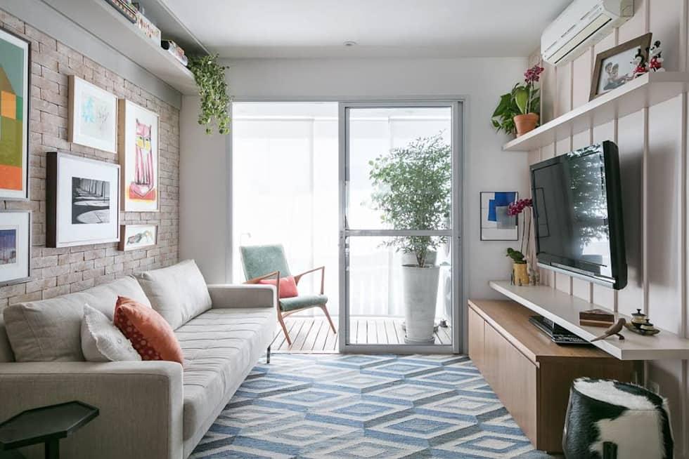 Sala com parede branca e outra de tijolo. Tapete azul, sofá bege. O rack é branco com madeira. A parede atrás do sofá tem seis quadros,