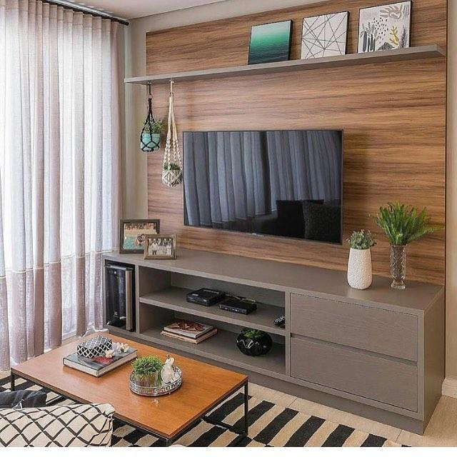 Sala com hack em madeira e cinza, decorado com uma TV, quadros e plantas. Mesa de centro de madeira e tapete geométrico.