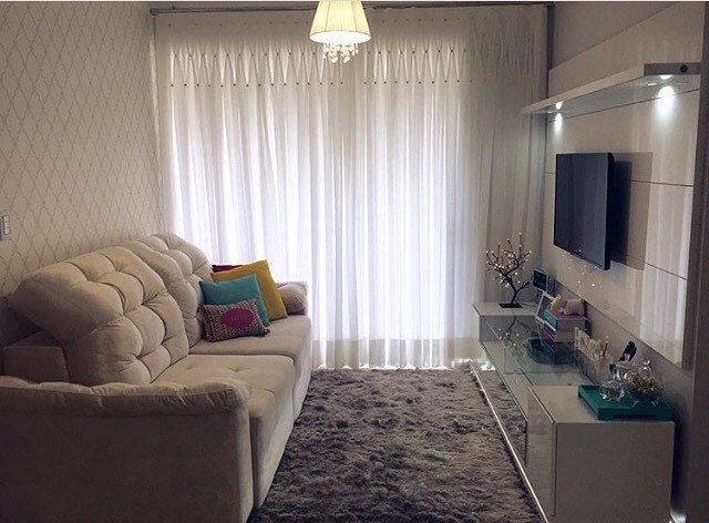 Ambiente com cortina branca, papel de parede atrás de um sofá bege, hack branco e com vidro com tv, almofadas coloridas e tapete felpudo.