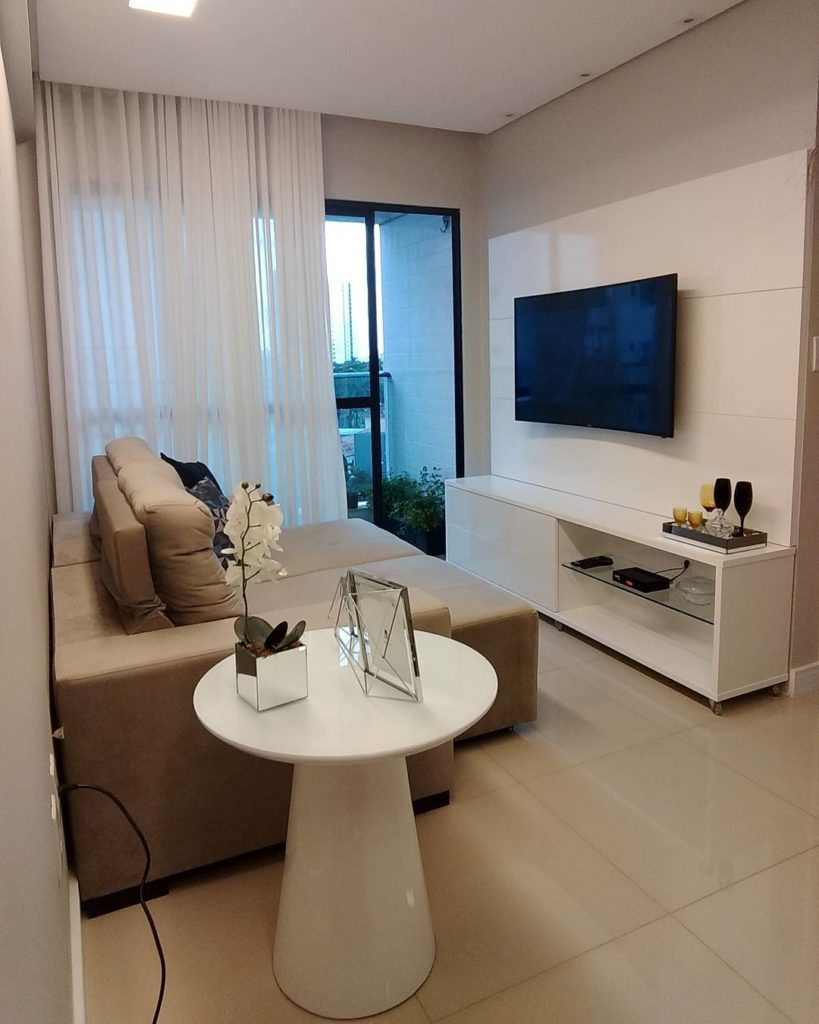 Sala minimalista com hack, cortina e mesa de canto brancos e sofá bege.