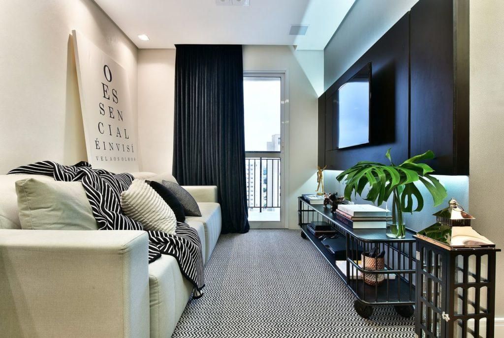 Sala com cortina preta, tapete preto e branco, hack de ferro e sofá bege.