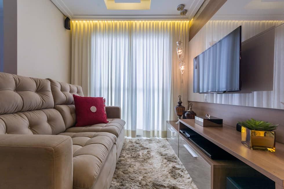 Sala toda bege, com almofada vermlha, rack, sofá e cortinas no mesmo tom e tapete de pelos.