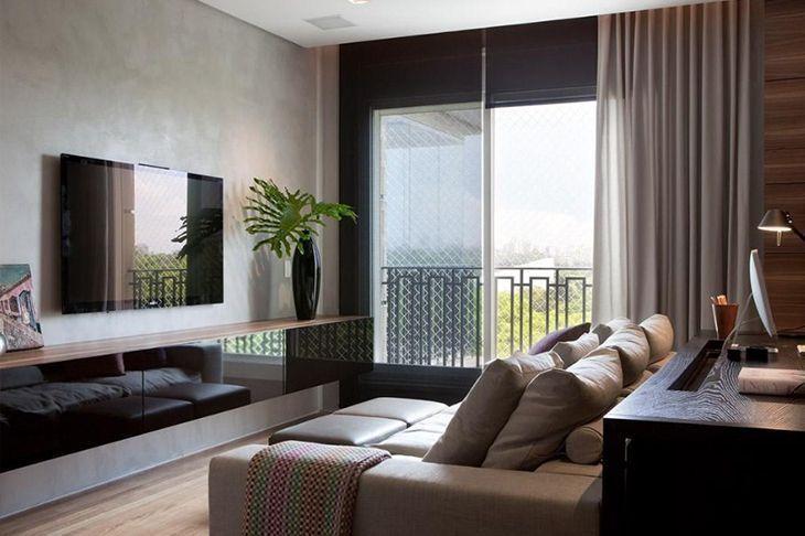Sala com janela ampla, hack espelhado, parede estilo cimento queimado, cortina cinza e sofá bege. No canto, em cima do hack, um vaso alto com uma planta.