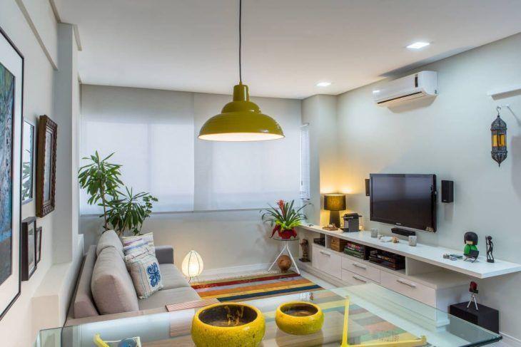 Sala clara, com sofá cinza claro e hack branco, assim como a cortina. O pé da mesa de jantar, os enfeites em cima da mesa e a luminária são amarelos.
