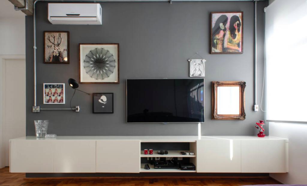 Parede cinza escuro, decorada com uma TV e quadros de tamanhos diversos. O hack é branco e o chão de taco.