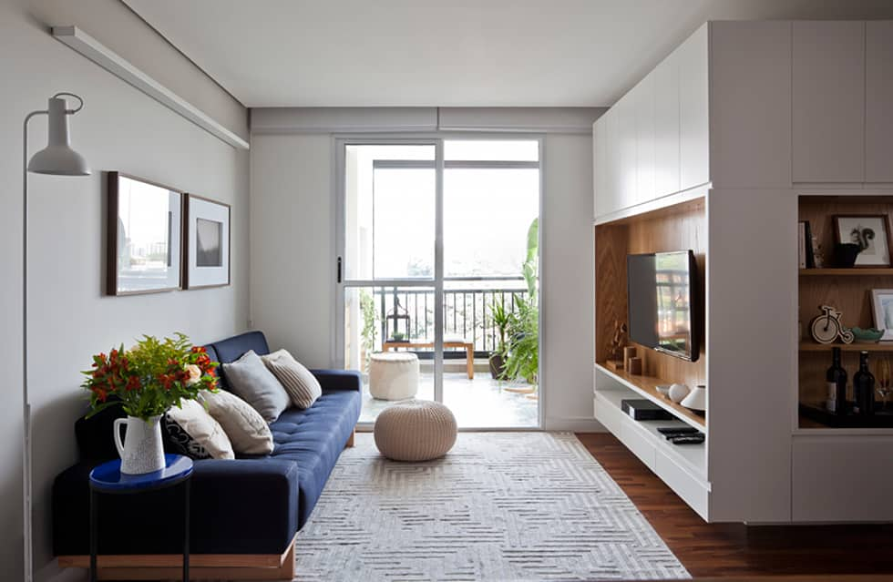 Sala bem iluminada, toda branca e sofá azul.
