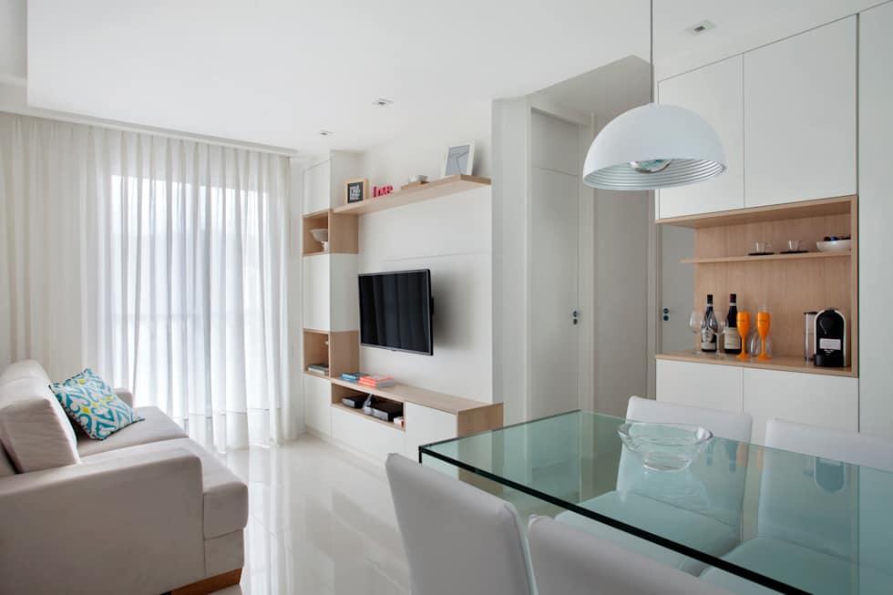 Comodo com paredes, sofá, cadeiras e rack brancos. A mesa é de vidro.