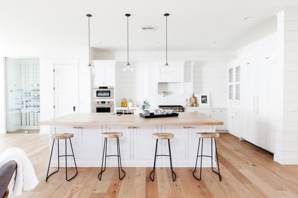 Cozinha branca com ilha de madeira.