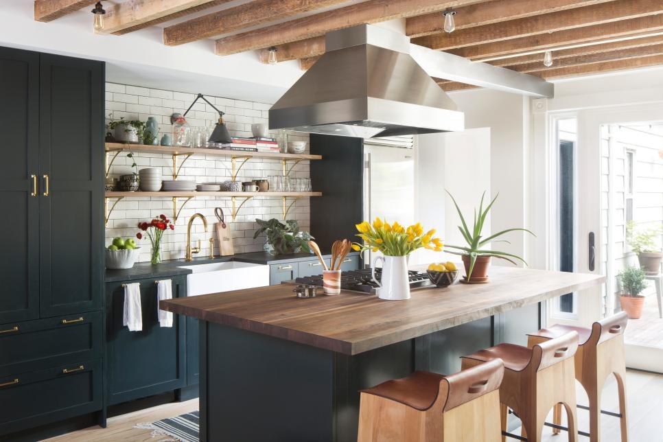 Cozinha preta com madeira.