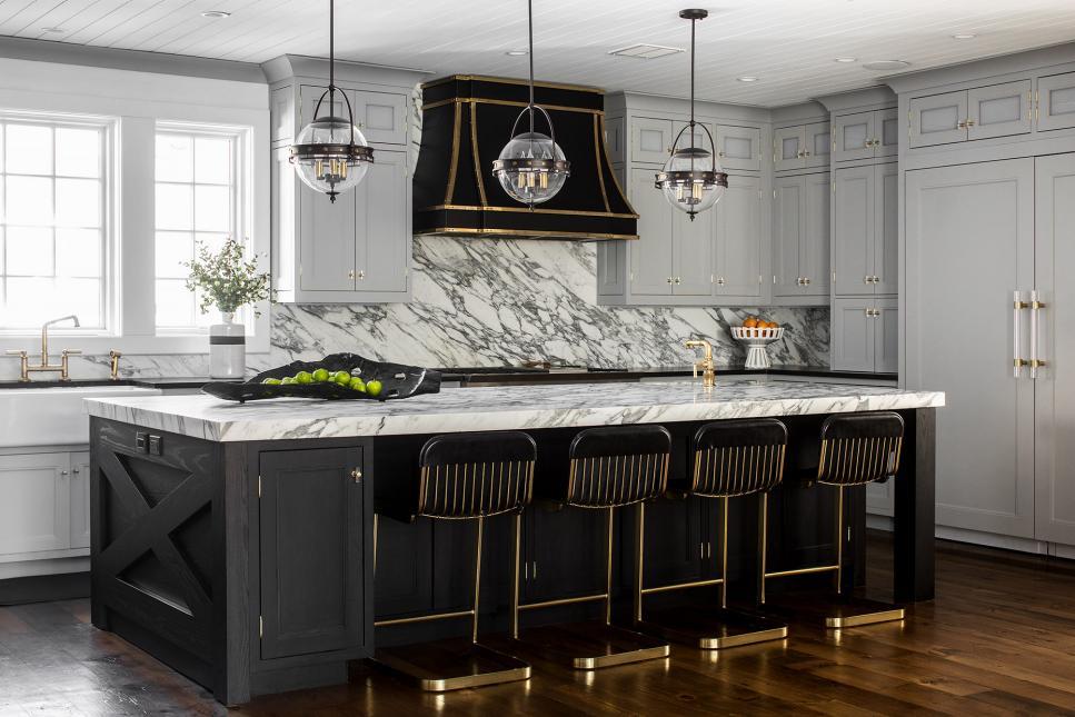 Cozinha com ilha e itens pretos e dourados,