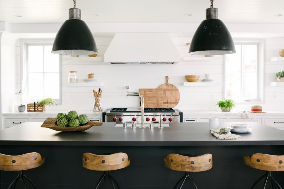 Cozinha branca com luminárias escuras e ilha preta.