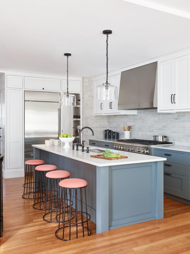 Cozinha com ilha branca, cinza e rosa.