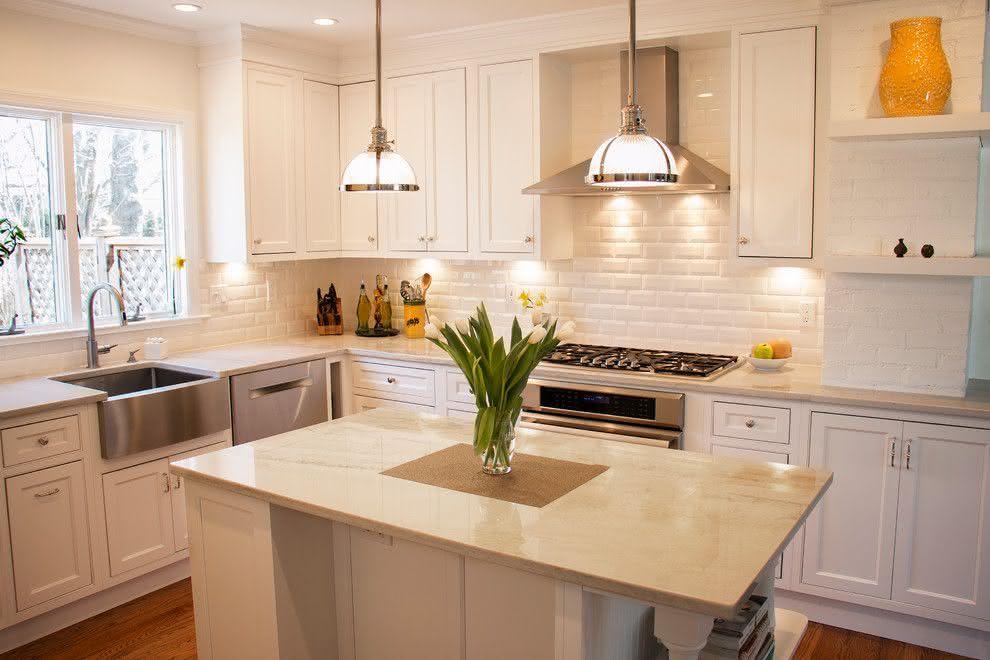 Cozinha com ilha branca e bege.