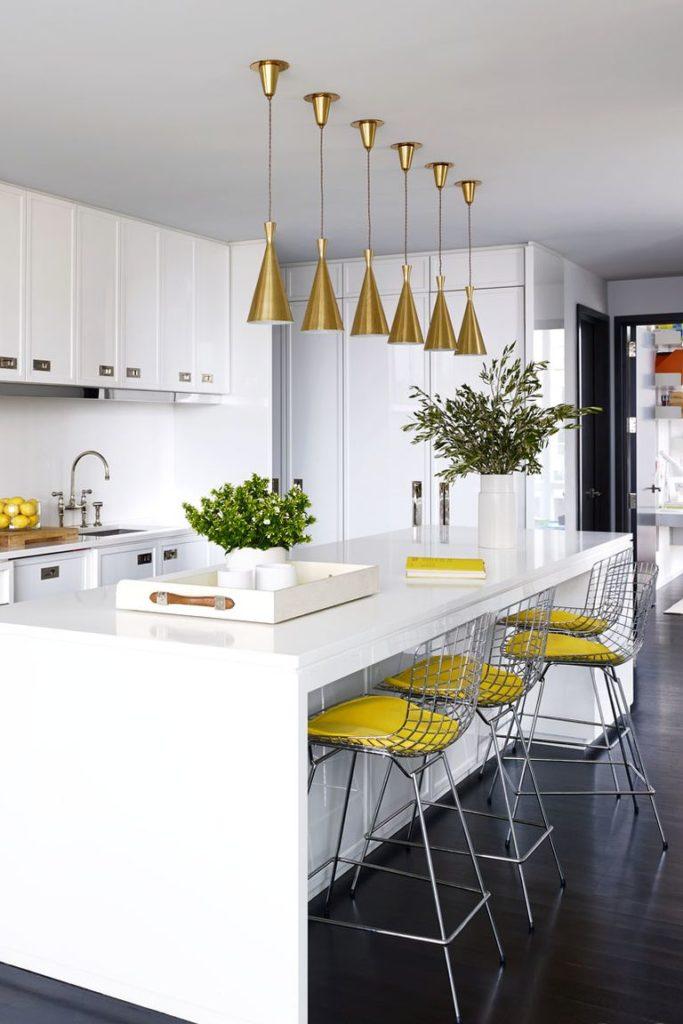 Cozinha branca com luminária dourada.