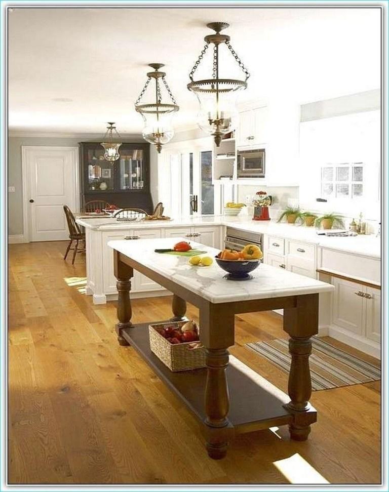 Ilha móvel em cozinha branca com madeira.