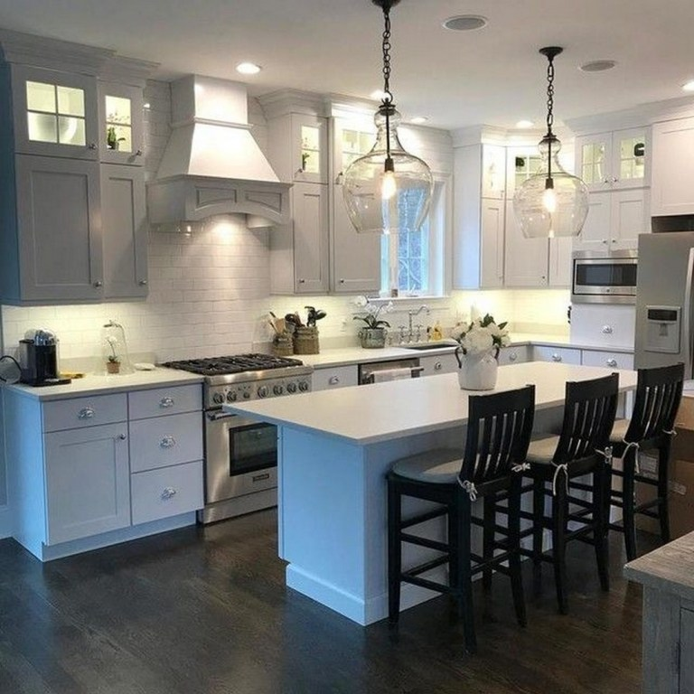 Cozinha com ilha cinza e branca.