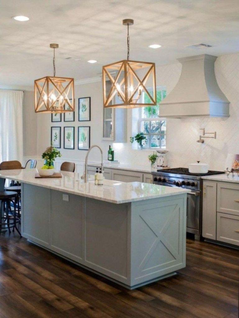 Cozinha com ilha e luminária de madeira.