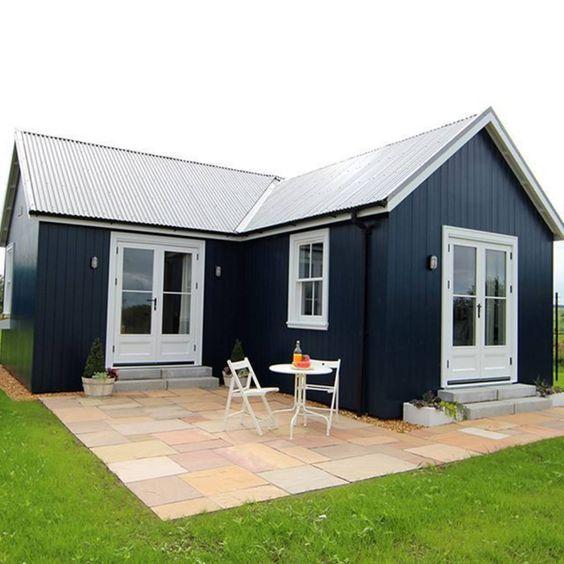 Casa de madeira com layout em L, paredes pretas e portas em branco.