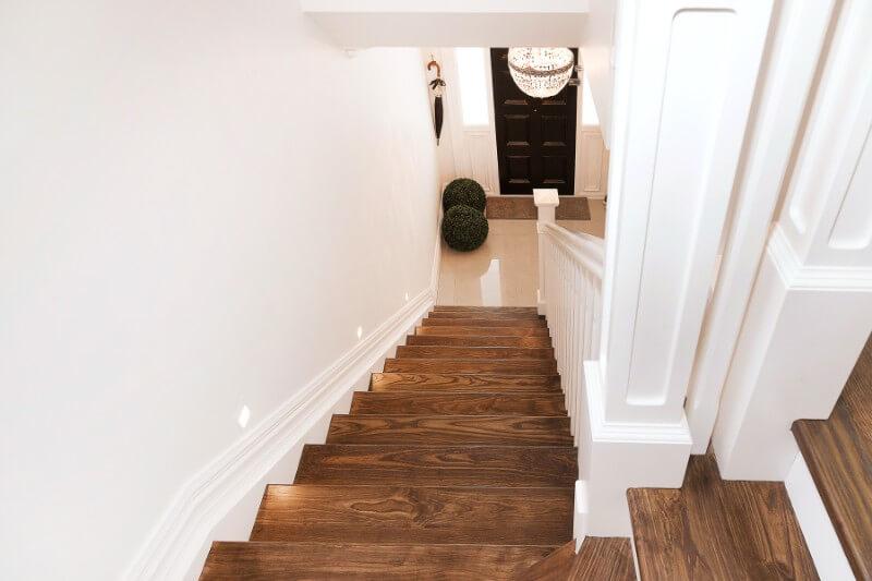 Escada de madeira com corrimão branco.