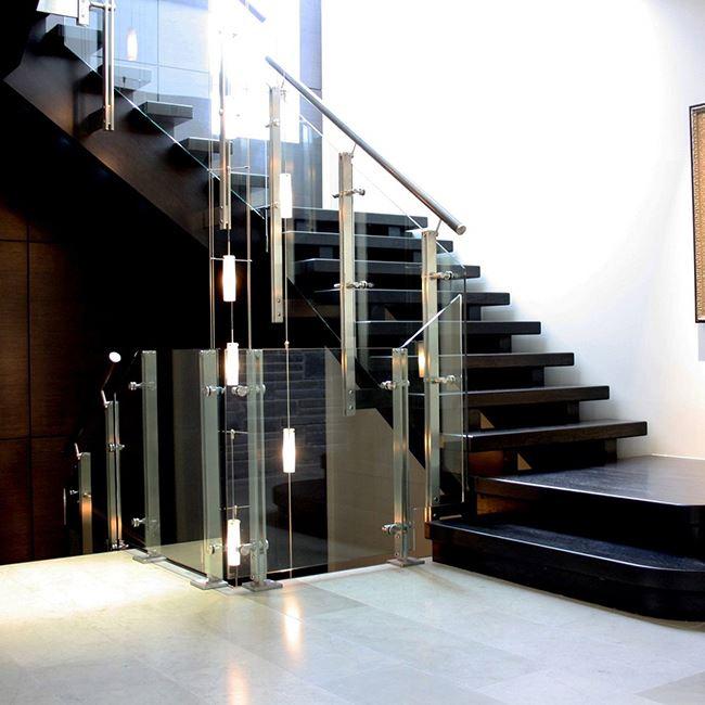 escada de madeira pintada de preto com corrimão de vidro e ferro