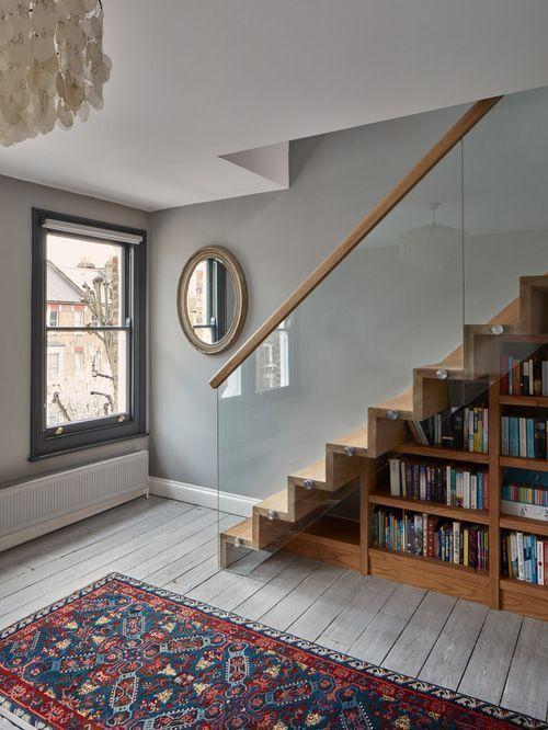 Escada de madeira e vidro, com estante embaixo.