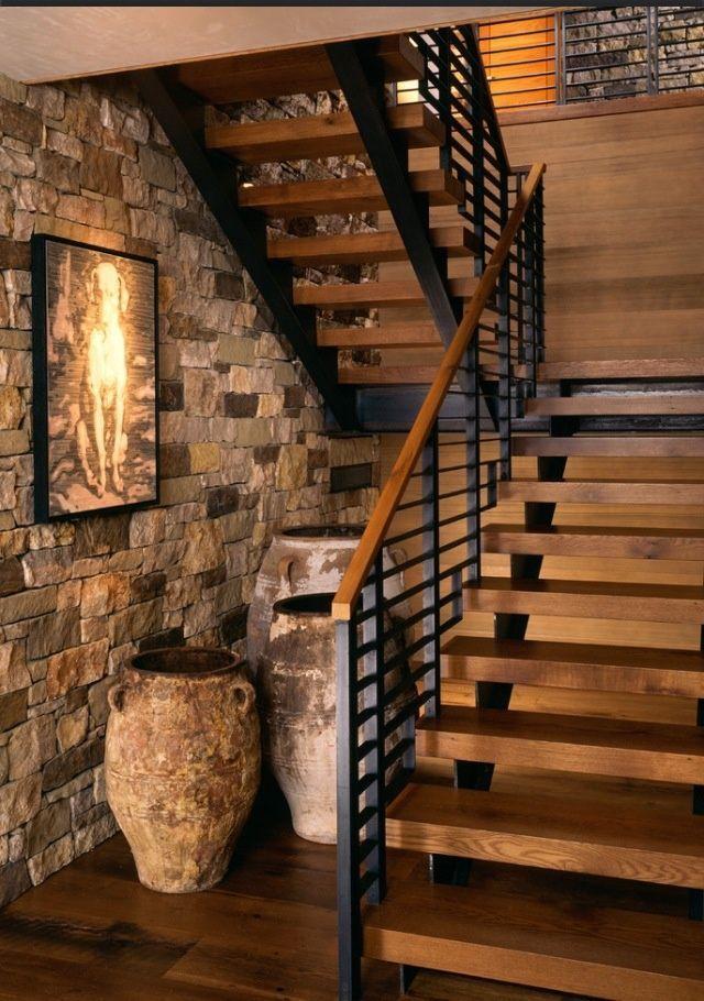 Escada de madeira com corrimão preto.