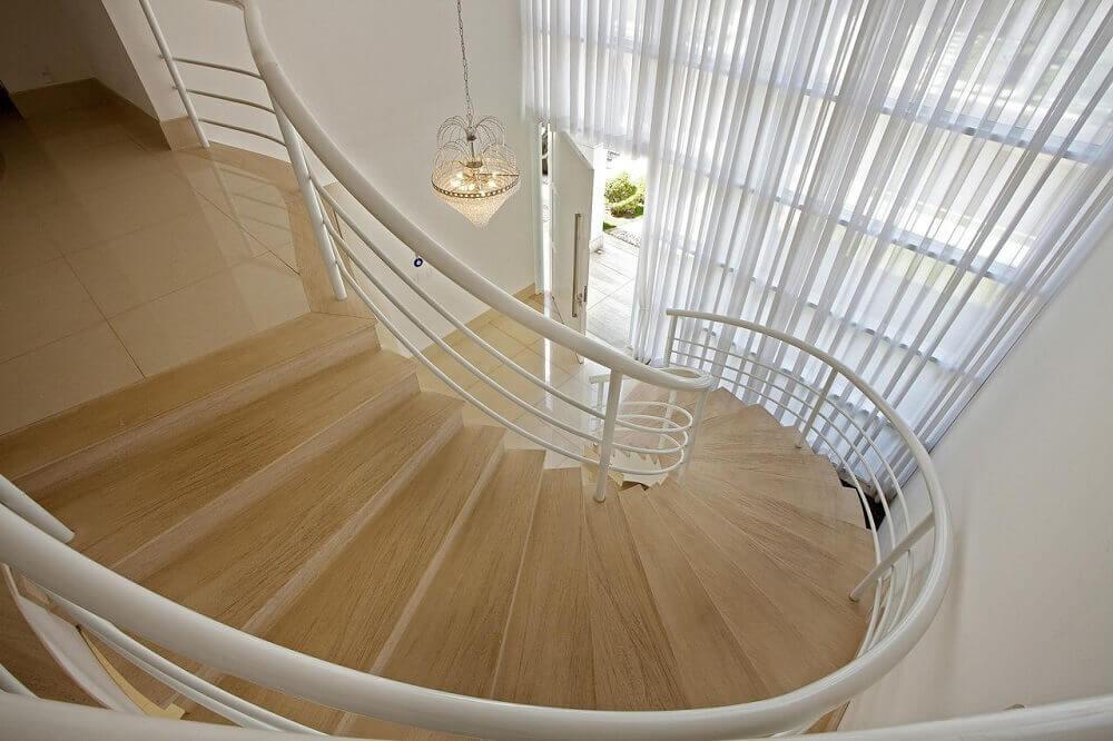 Escada caracol com corrimão branco.