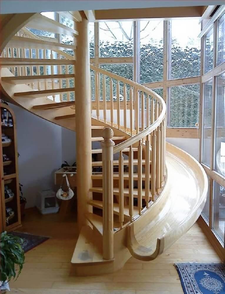 Escada de madeira em formato de caracol, com escorrega do lado