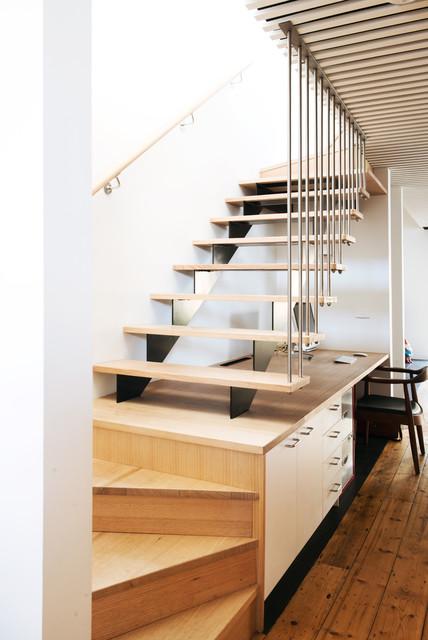 Escada de madeira com guarda corpo vertical.