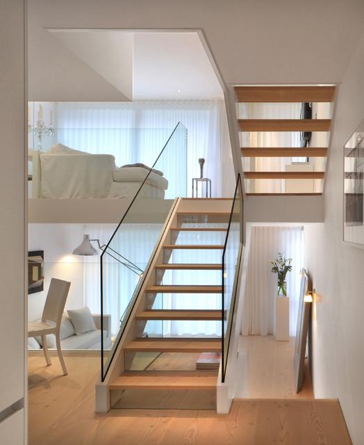 Escada em U com corrimão de vidro.