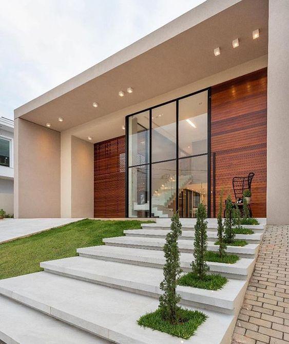 Fachada com telhado embutido, madeira e abertura de vidro.