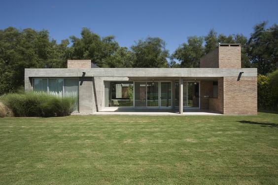 Fachada térrea com arquitetura modernista, concreto aparente e tijolinho.