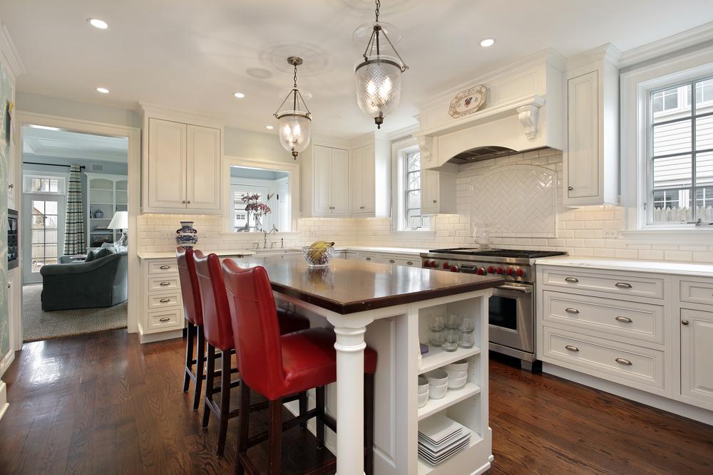 Cozinha de ilha branca com cadeiras vermelhas.