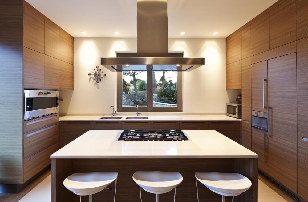 Cozinha com ilha e revestimento de madeira.
