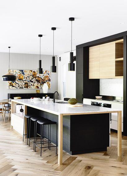 Cozinha com ilha preta, branca e de madeira.