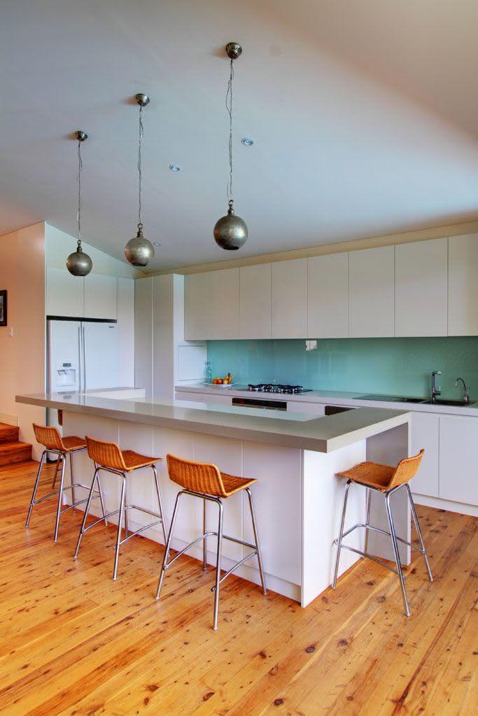 Cozinha com ilha e luminária moderna.