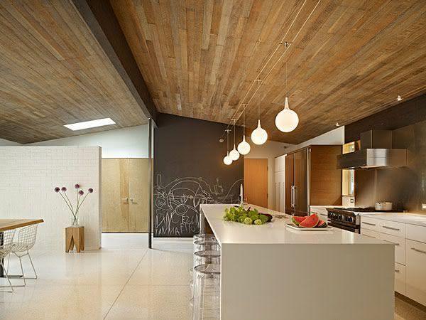 Cozinha com ilha e teto de madeira.